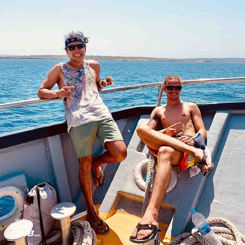 happy guys sitting on a boat in ibiza