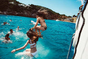 girls jumping in the sea of the ibiza boat club