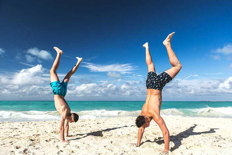 men at the beach doing hand stand
