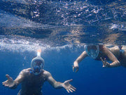 couple snorkelling with full face masks in the sea