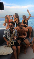 girls drinking champagne on a catamaran and guy with saxophone