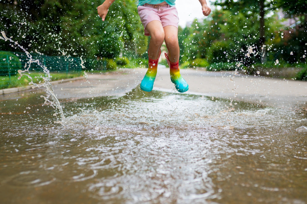Child jumps in puddle wearing boots