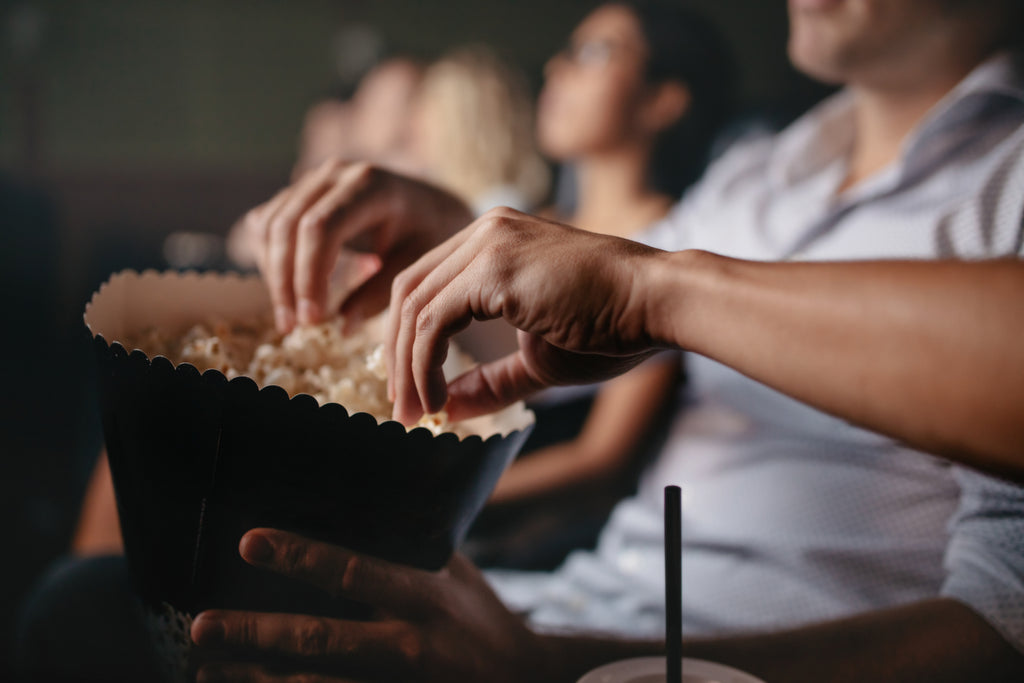 Young people eating popcorn at the movies