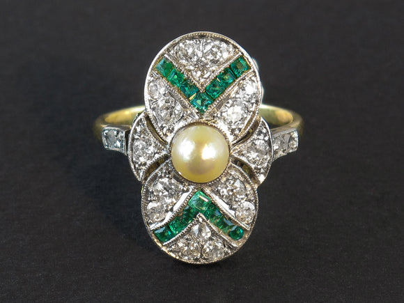 An Art Déco gold platinum diamond and emerald ring centering a natural pearl