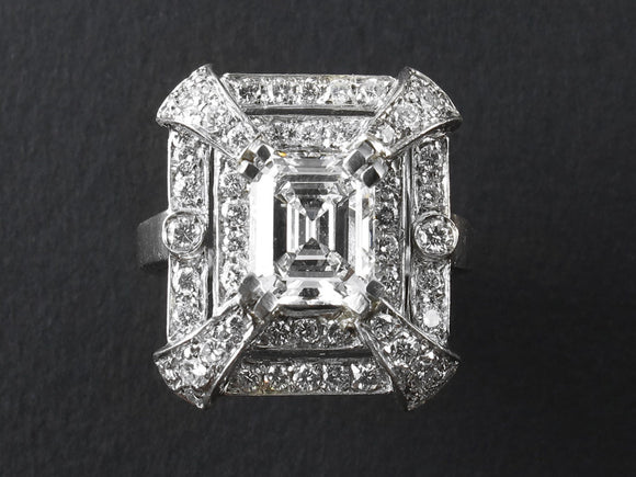 An Art Déco platinum and diamond ring of rectangular design, centering an emerald-cut diamond ring