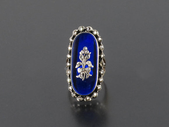 A Georgian XIX Century Yellow gold and silver ring with rose-cut diamonds and blue glass.