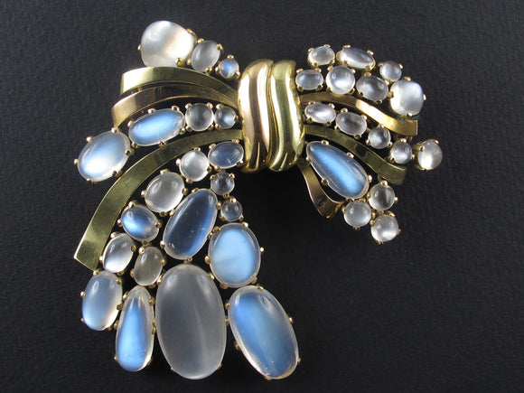 A yellow and rose gold ribbon brooch with moonstones. USA, 1940