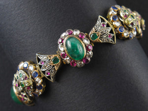 An Egyptian revival gold and silver bracelet with rubies, sapphires, emeralds and rose-cut diamonds. 1900 c.a.
