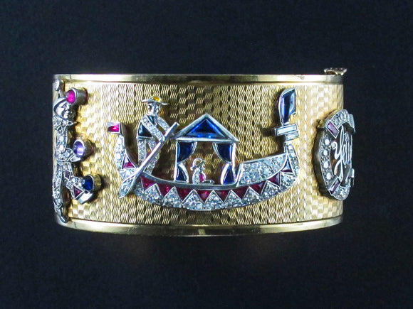An Art Déco rare Yellow gold and platinum cuff bracelet with seven diamond and precious stone charms. USA, 1940 c.a.