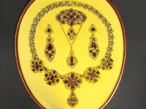 A XIX Century Georgian gold repoussé and canetille parure set with foiled garnets.