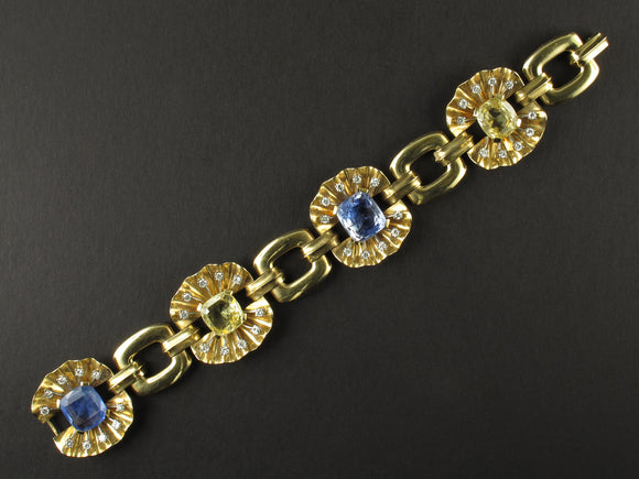 A yellow gold, diamond and yellow/blue sapphire bracelet. Period 1950 circa