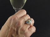 An Art Déco yellow gold platinum diamond and emerald ring centering a natural pearl
