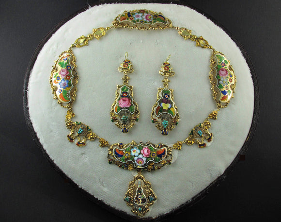 A yellow gold en repoussé enameled parure. Composed of a necklace and a pair of earrings of flowers design. In original fitted box. Napoli XIX Century
