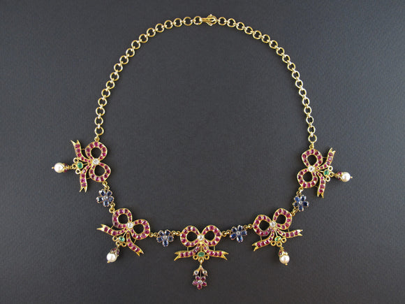 A festive yellow gold, ruby, diamond, pearls and sapphire vintage necklace, the ribbons are XIX century
