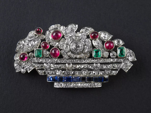 An Art Déco platinum diamond, ruby emerald and sapphire basket brooch. France, 1925 c.a.
