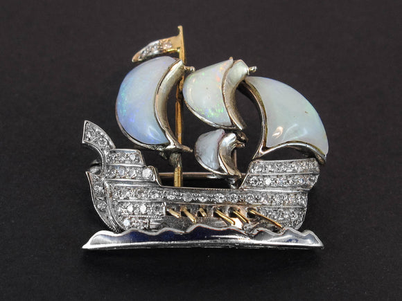 A platinum, gold, diamond and opal brooch in the shape of a caravel with rows on the waves. 1930 c.a.