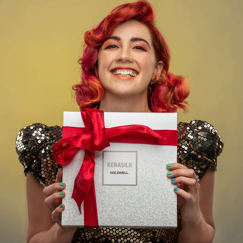 Red haired woman smiling holding red ribbon tied Christmas gift set