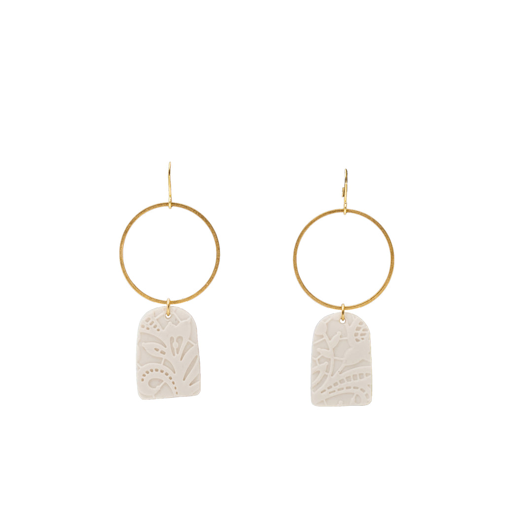 White clay design earrings with brass accent.