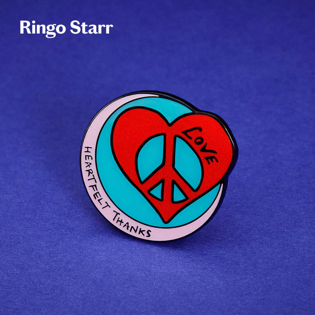 Ringo Starr pin badge with heart, peace and love symbol photographed on an blue background