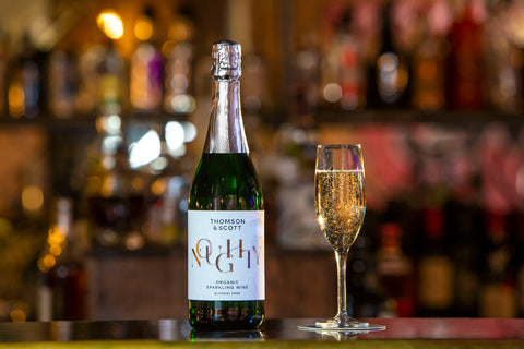 Noughty – the alcohol-free sparkling wine by Thomson & Scott – standing on a bar next to a glass