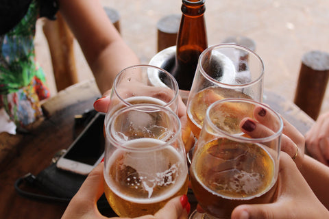 Group of people clinking glasses of alcohol-free beer