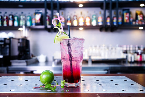 Non-alcoholic drink garnished with lime standing on a bar