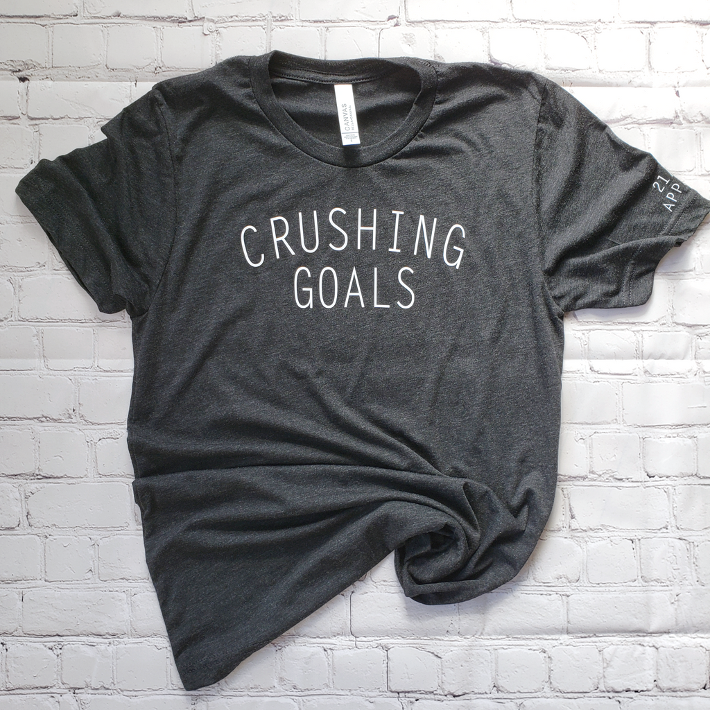 flatlay of charcoal black unisex triblend crushing goals t shirt
