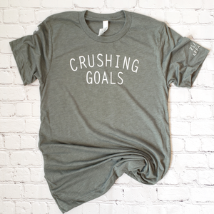 flatlay of army green unisex triblend crushing goals t shirt