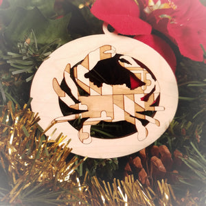 Laser engraved birch Christmas ornament featuring a blue crab with the Maryland state flag design