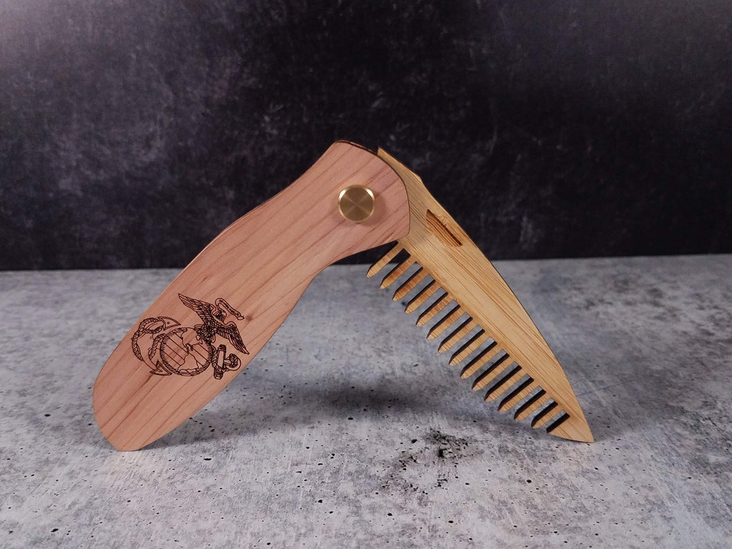 Folding tactical beard comb featuring a cedar handle laser engraved with a United States Marine Corps (USMC) Eagle Globe and Anchor (EGA), and a bamboo ply blade