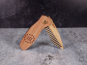 Folding tactical beard comb featuring a cedar handle laser engraved with a Three Percenter symbol, and a bamboo ply blade