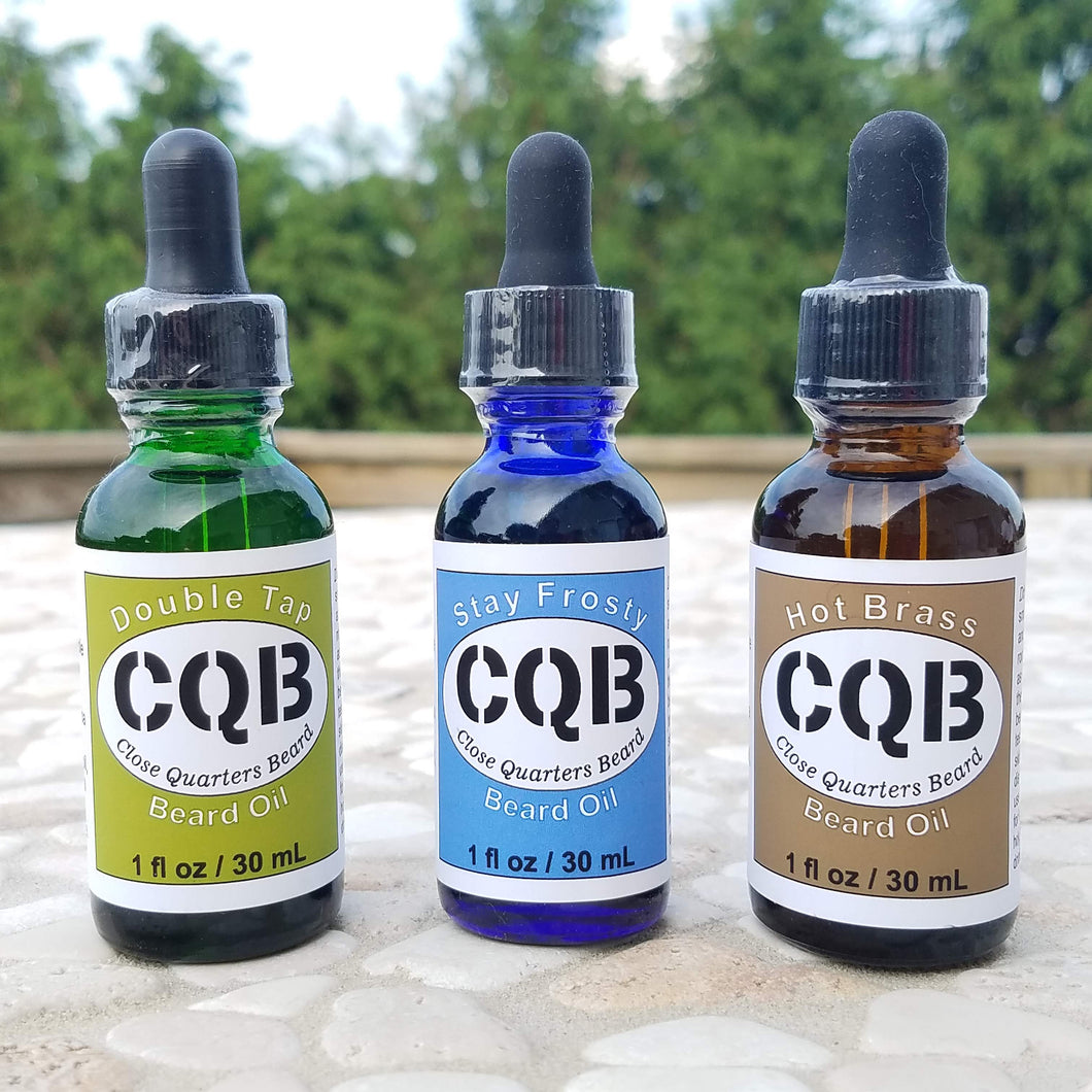 A selection of Close Quarters Beard oil scents: Double Tap, Stay Frosty, and Hot Brass