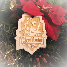 Load image into Gallery viewer, Laser engraved birch Christmas ornament with the Harry Potter Hogwarts House crest of Gryffindor. Add custom engraved text to the back for a personalized touch.