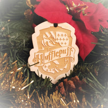 Load image into Gallery viewer, Laser engraved birch Christmas ornament with the Harry Potter Hogwarts House crest of Hufflepuff. Add custom engraved text to the back for a personalized touch.
