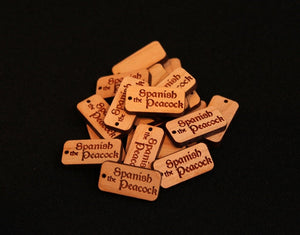 "1"" x .5"" custom laser engraved tags cut from hardwoods. Tags can be used for product branding, packaging, or gift bags."