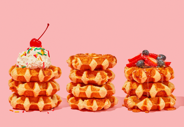 Three stacks of Belgian Waffles with toppings such as ice cream, fruit, and syrup.