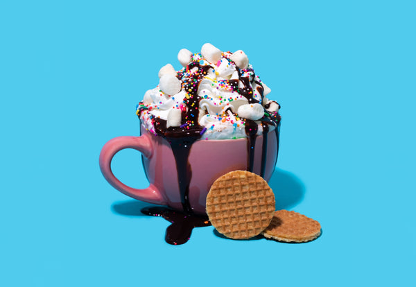Hot chocolate with whipped cream, marshmallows, sprinkles, and chocolate syrup. Paired with a mini stroopwafel.