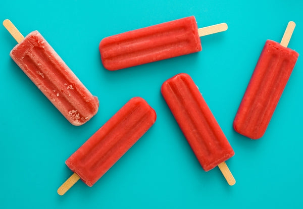 Strawberry popsicles over a bright blue backdrop