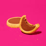 One and a half Choco Caramel Cookie Tarts produced by Belgian Boys on a pink background