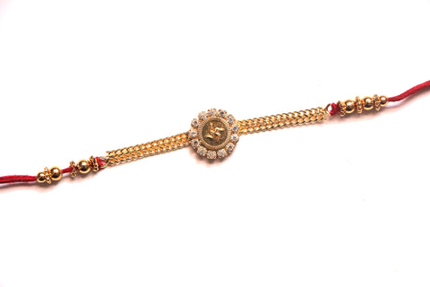 Gold finish swastik rakhi with white crystals - OnlinePrasad.com