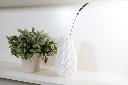 White Vase next to green plant