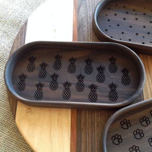 Walnut catchall tray with pineapples engraved on the bottom of the tray