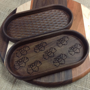 Two walnut catchall trays one has a bunch of acorns engraved on the bottom, the other has carved bottom