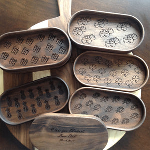 five walnut catchall trays with different engravings on the bottom of tray, pineapples, acorns, four leaf clovers and roses  by Michael's Woodcrafts Greenville SC woodworker Woodworking artist woodworkers