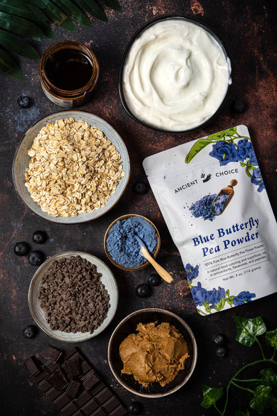 Ingredients on a table: butterfly pea flower powder, nut butter, oats, chocolate, and yogurt