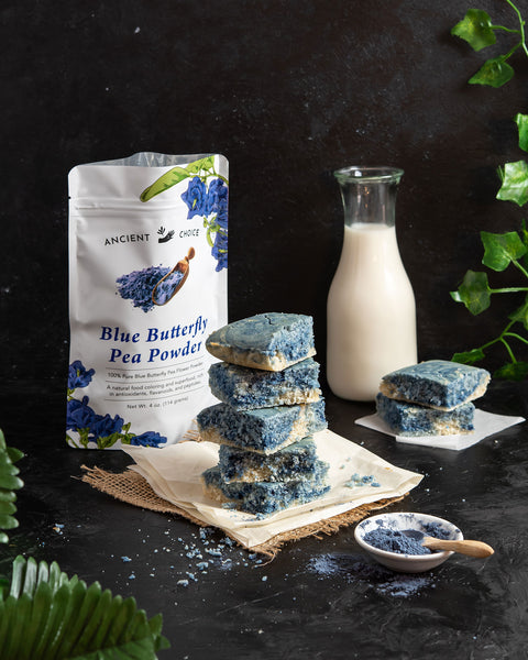 Stacked butterfly swirl cake pieces in front of a bag of Ancient Choice butterfly pea flower powder