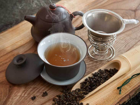 steaming cup of oolong tea next to teapot and other utensils