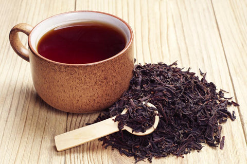 black tea in a brown cup next to a heap of dried black tea leaves