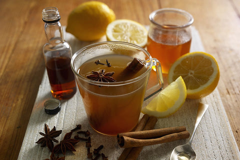 A cup of hot toddy surrounded with ingredients