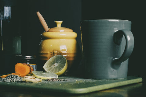 A pot of honey, slices of lemon, and other ingredients next to a mug